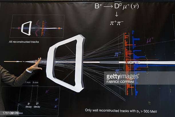 A scientist gestures next to a banner at the European Organisation for Nuclear Research Large Hadron Collider on July 19 2013 in Meyrin near Geneva...