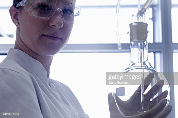 scientist holding beaker in lab - sigrid gombert stock pictures, royalty-free photos & images