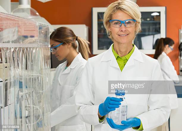 scientist holding beaker in laboratory - scienziata foto e immagini stock