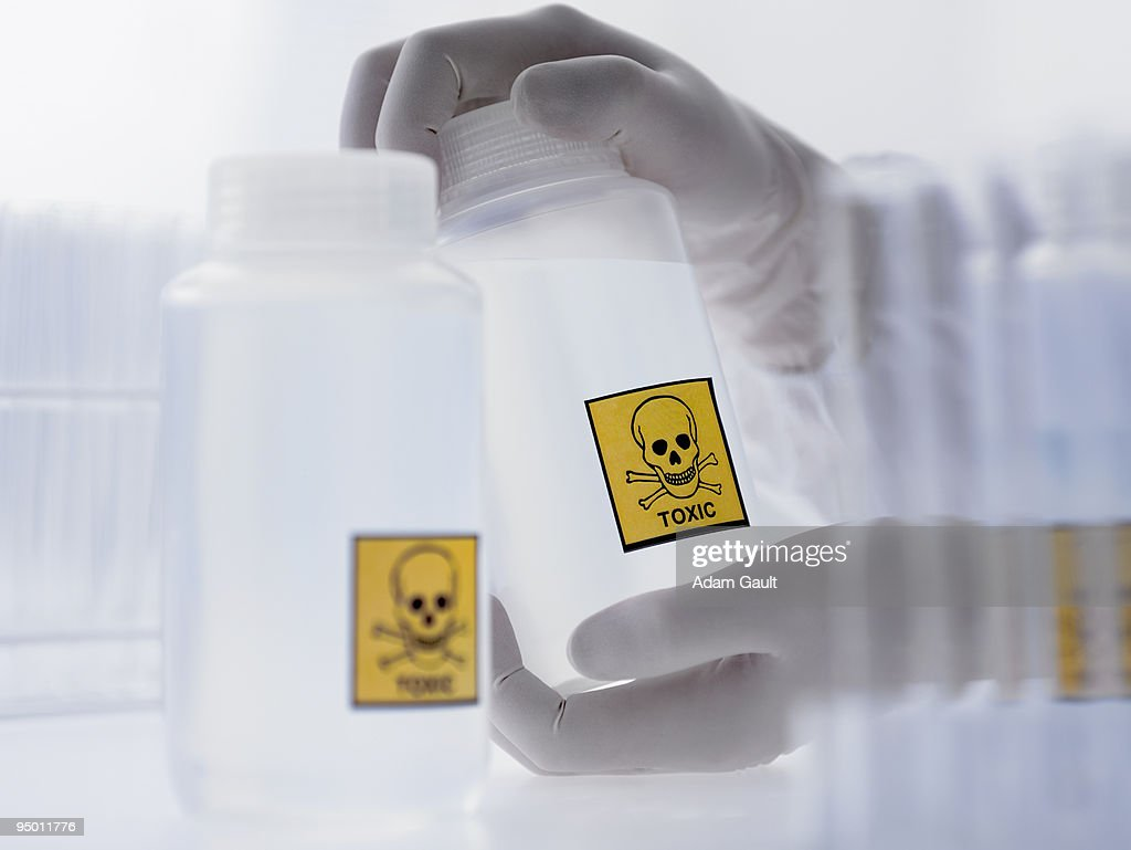 Scientist holding bottle with toxic label : Stock Photo