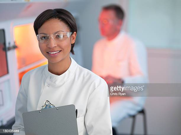 scientist holding clipboard in lab - eye protection stock pictures, royalty-free photos & images
