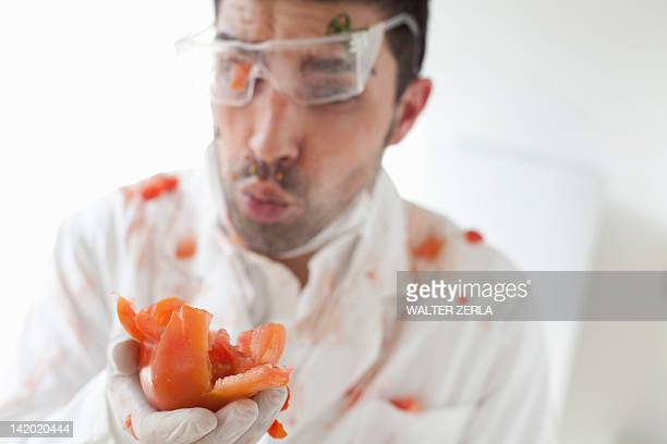 Scientist holding exploding tomato