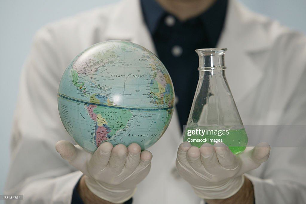 Scientist holding globe and beaker : Stockfoto