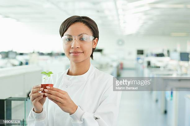 Scientist holding plant in lab