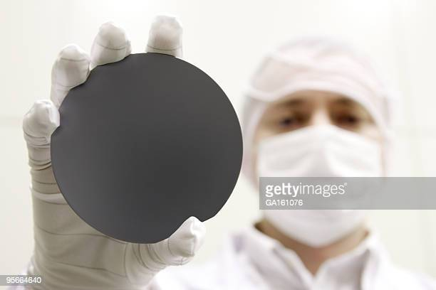 A scientist holding up a black circle to the camera