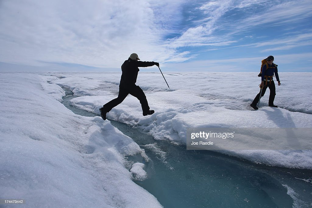 Scientist Ian Joughin of the University of Washington leaps over a small meltwater stream as he walks with Graduate Student, Laura Stevens, from the Massachusetts Institute of Technology and Woods Hole Oceanographic Institution as they conduct research on July 16, 2013 on the Glacial Ice Sheet, Greenland. The scientists set up Global Positioning System sensors to closely monitor the evolution of the surface lakes and the motion of the surrounding ice sheet. As the sea levels around the globe rise, researchers affilitated with the National Science Foundation and other organizations are studying the phenomena of the melting glaciers and its long-term ramifications. The warmer temperatures that have had an effect on the glaciers in Greenland also have altered the ways in which the local populace farm, fish, hunt and even travel across land. In recent years, sea level rise in places such as Miami Beach has led to increased street flooding and prompted leaders such as New York City Mayor Michael Bloomberg to propose a $19.5 billion plan to boost the citys capacity to withstand future extreme weather events by, among other things, devising mechanisms to withstand flooding.