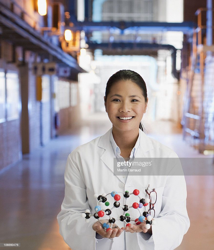 Scientist in factory holding molecule model : Stock Photo