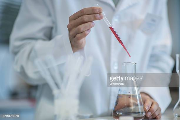 Scientist in lab pipetting into Erlenmeyer flask