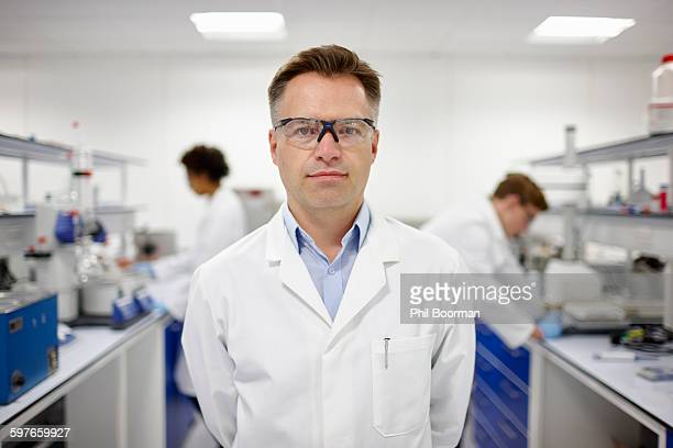 scientist in laboratory, colleagues working in background - laborkittel stock-fotos und bilder