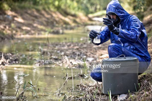 scientist in protective workwear examining water sample - environmentalist stock pictures, royalty-free photos & images