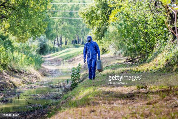 Scientist in Protective Workwear Standing on Creekbank
