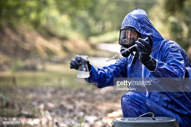 Scientist in Protective Workwear Taking a Water Sample