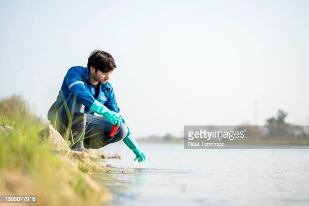 scientist in white safety suit examining polluted waste. environment scientist examining water and collecting water samples (ph value). - examining stock pictures, royalty-free photos & images