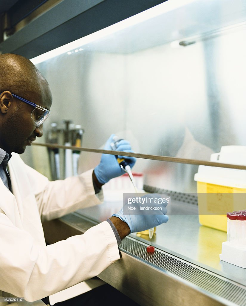 Scientist Injecting Fluid into a Container : Stock Photo