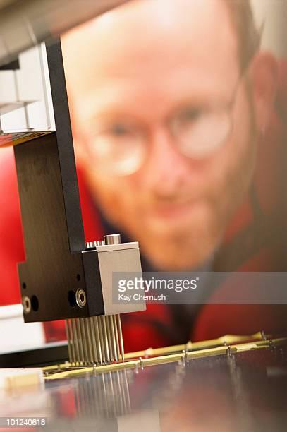 Scientist inspecting machine