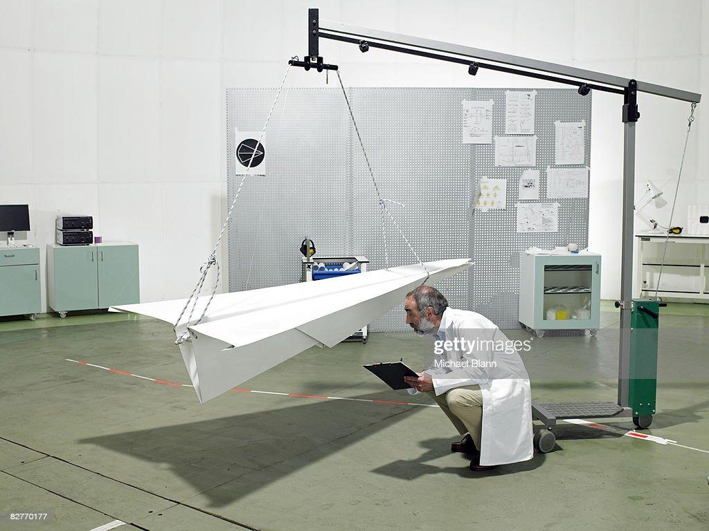 Scientist inspecting paper plane in laboratory : Stock Photo