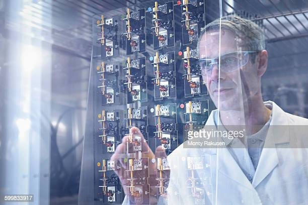 Scientist inspecting test lithium ion batteries in heat chamber in battery research facility