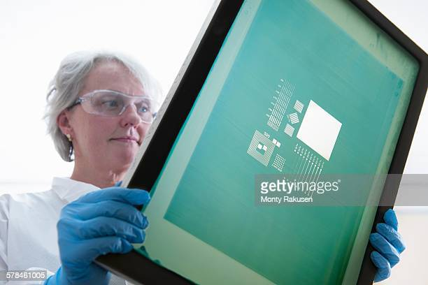 Scientist inspects screen printer mesh for graphene ink in graphene processing factory, close up
