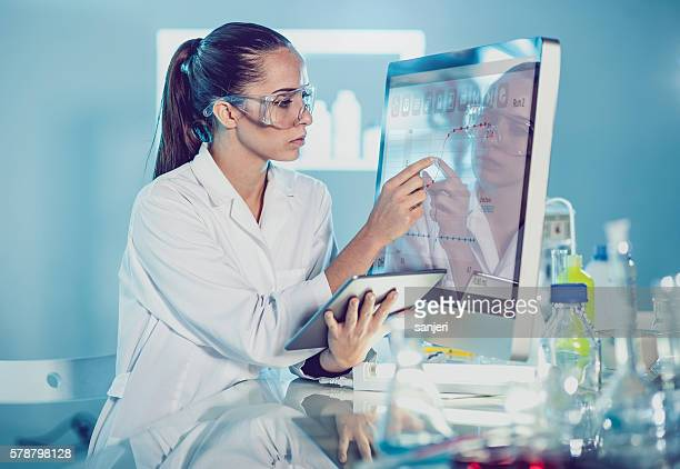 scientist interacting with the computer via touch screen - forense fotografías e imágenes de stock