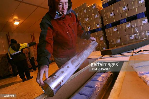 US scientist Lonnie Thompson inspects cylinders containing Papua glacier ice core samples on its arrival at a freezer storage in Jakarta on July 2...