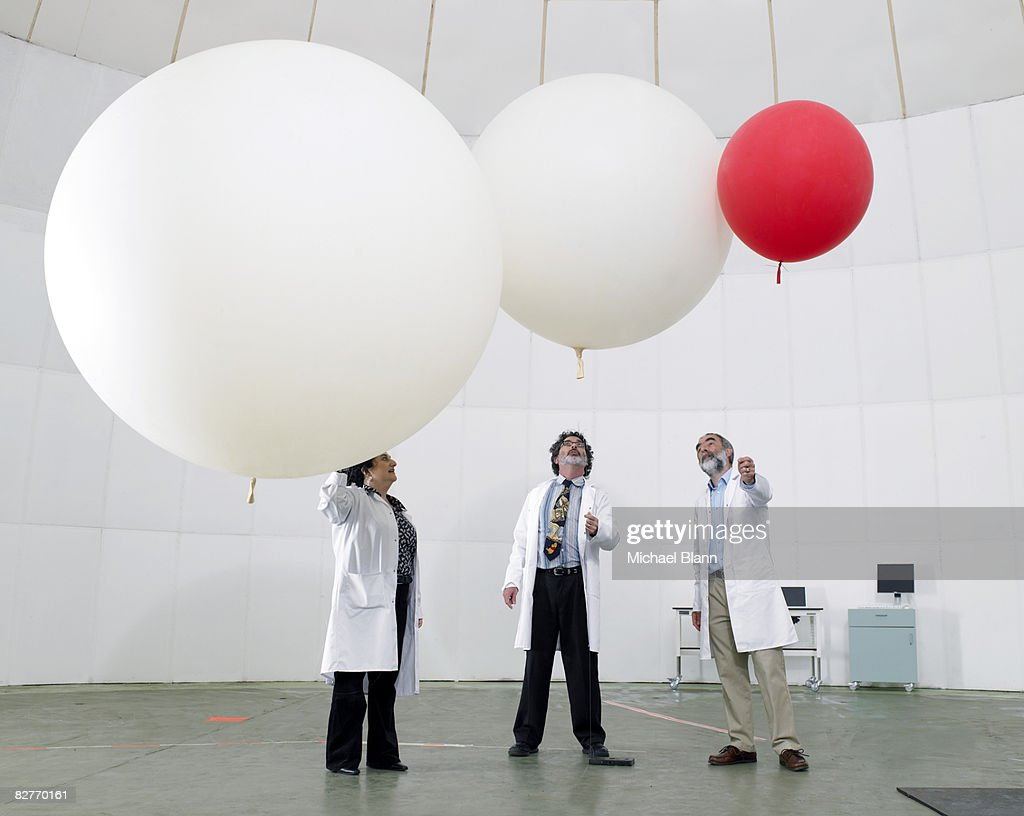 Scientist look upwards at balloons : Stock Photo