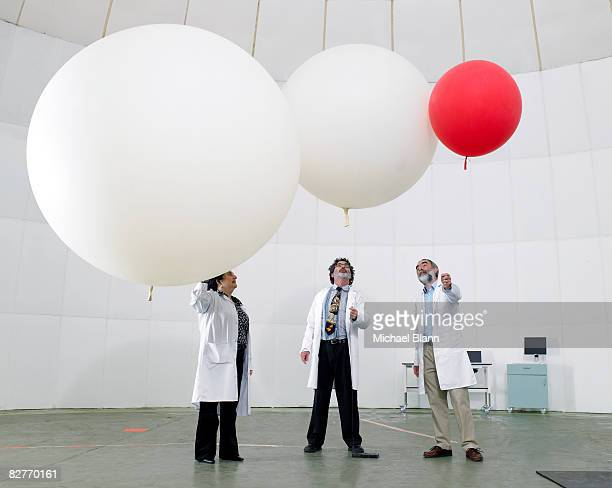 Scientist look upwards at balloons