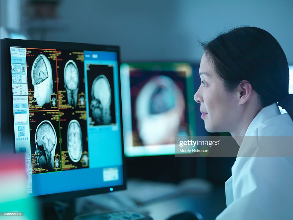 Scientist looking at 3D rendered graphic scans from Magnetic Resonance Imaging (MRI) scanner, close up : Stock Photo