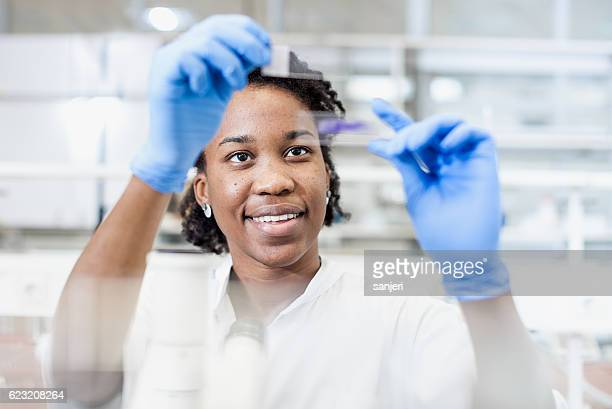 Scientist Looking at a Microscope Slide