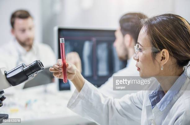 scientist looking at test tube - oncology stock photos and pictures