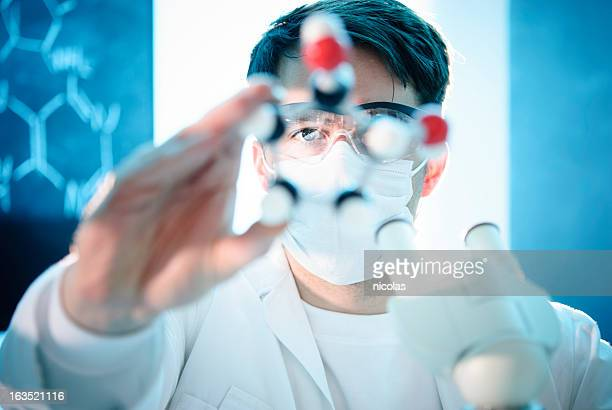 Scientist looking at the model of a molecule