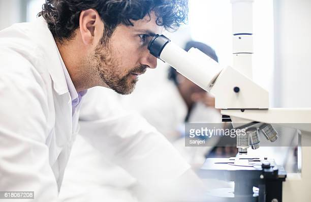 Scientist Looking into the Microscope