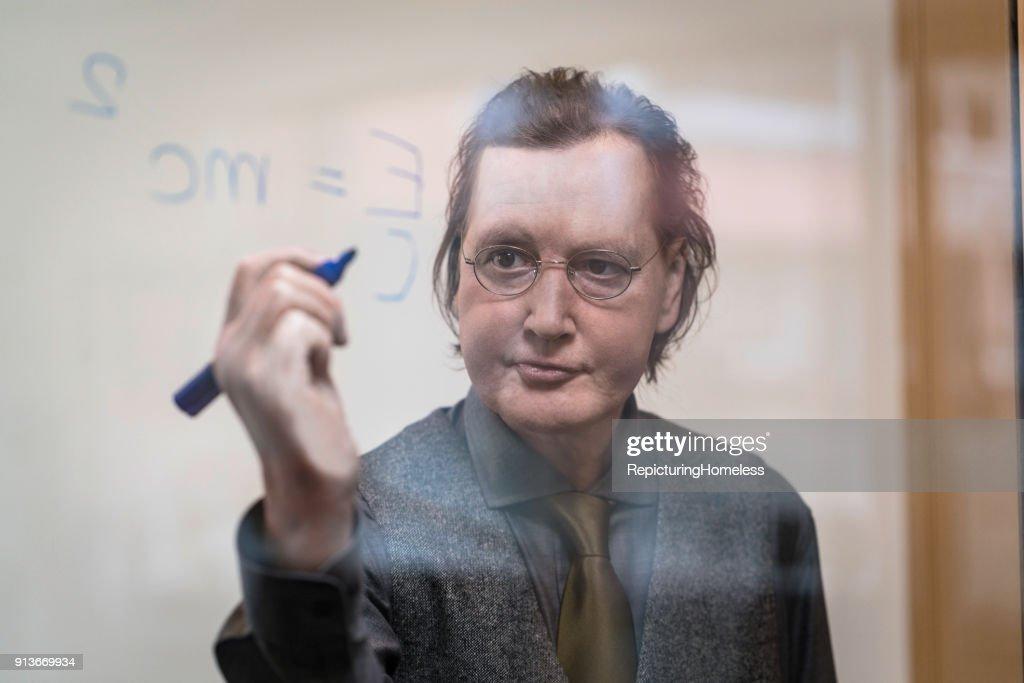 Ein Wissenschaftler schreibt gut gelaunt eine Formel auf eine Tafel : Stock-Foto