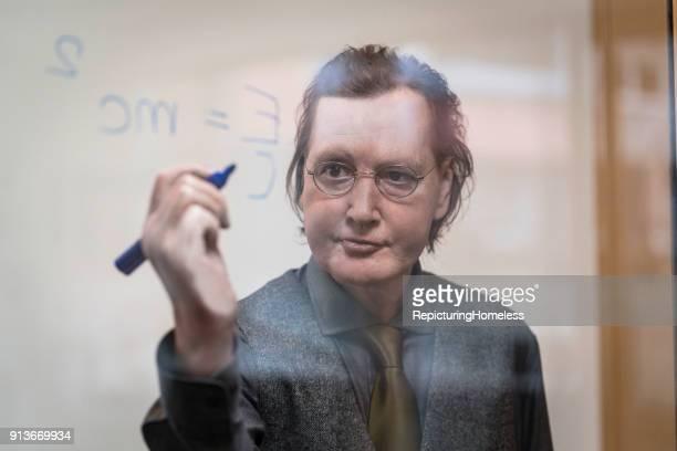 Ein Wissenschaftler schreibt gut gelaunt eine Formel auf eine Tafel