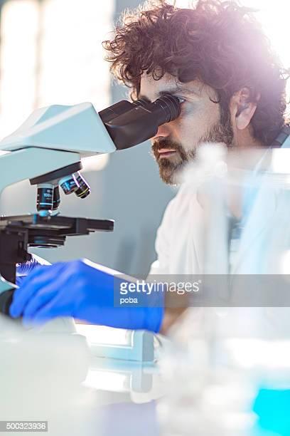 Wissenschaftler auf der Suche durch Mikroskop