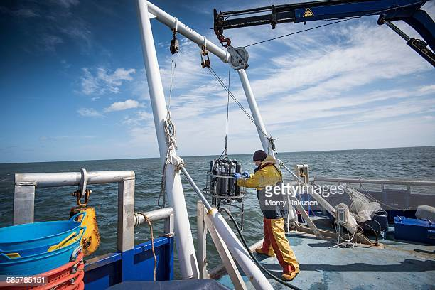 Scientist lowering sea water sampling experiment into sea on research ship