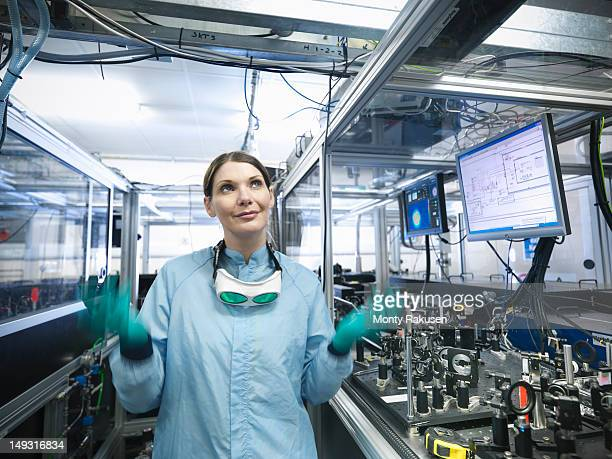 scientist making juggling motions by monitors with laser beam profiles and labview code - monty rakusen stock pictures, royalty-free photos & images