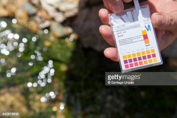 scientist measuring the ph on a contaminated river - ph value stock pictures, royalty-free photos & images