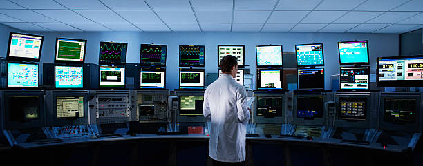 Scientist monitoring computers in control room