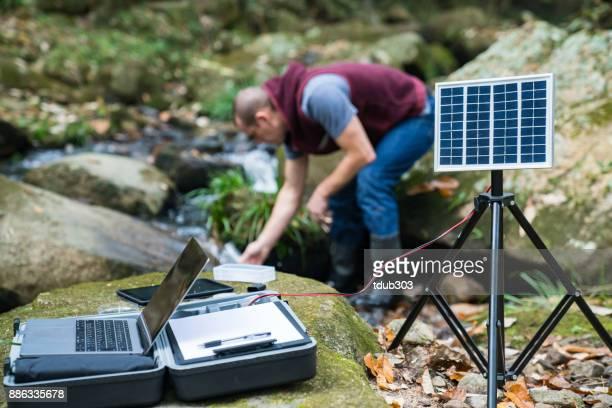 太陽動力を与えられたフィールド研究所から水質を監視する科学者