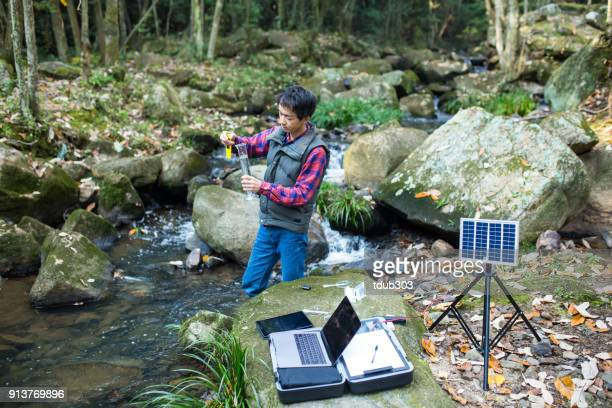 A scientist monitoring water quality from a solar powered field laboratory