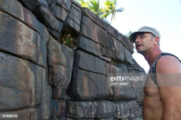 Scientist of the TerreOcean mission French geologist Eric Gilli poses in front of a rock on February 13 on the Devil's Island in the Caribbean Sea...