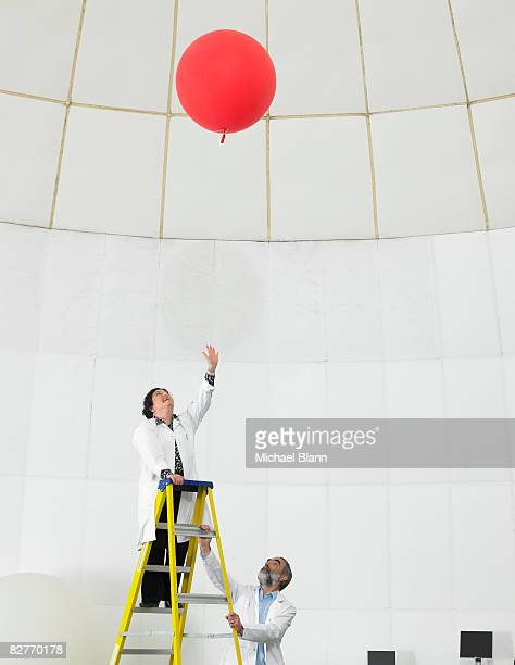 scientist on ladder watches balloon float away - weather balloon stock pictures, royalty-free photos & images