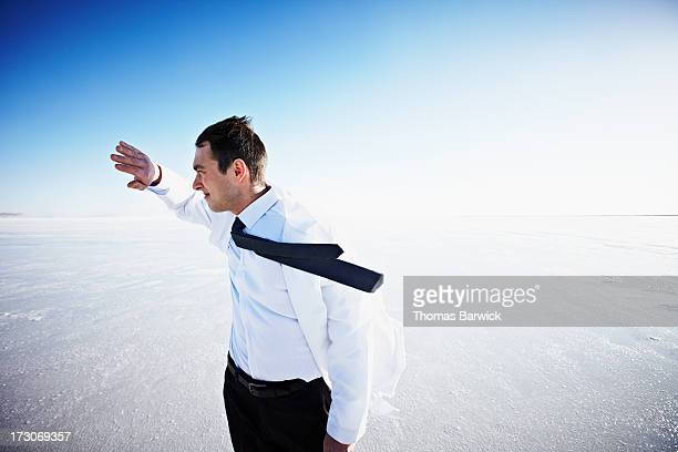 Scientist on windy salt flat hand in front of face