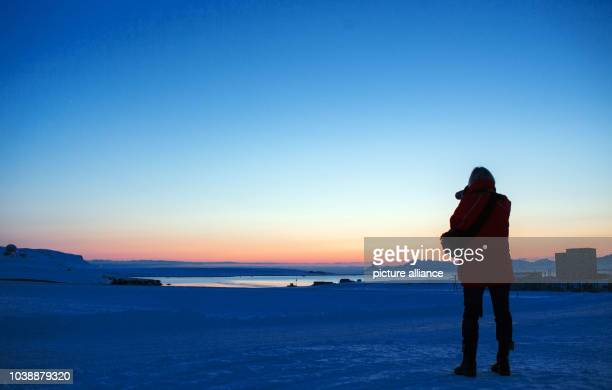 A scientist photographs the red sky of the polar night just before midnight at the atmosphere observatory of the resarch station Kings Bay in...
