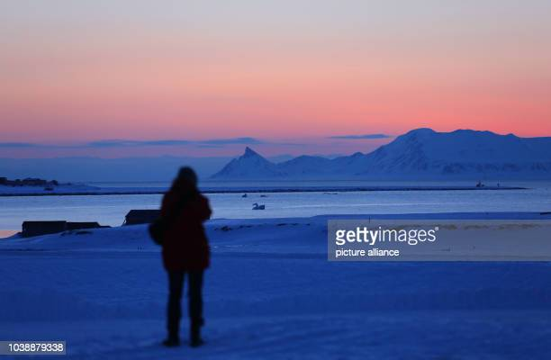 A scientist photographs the red sky of the polar night just before midnight at the resarch station Kings Bay in NyÅlesund on Spitsbergen Norway 09...
