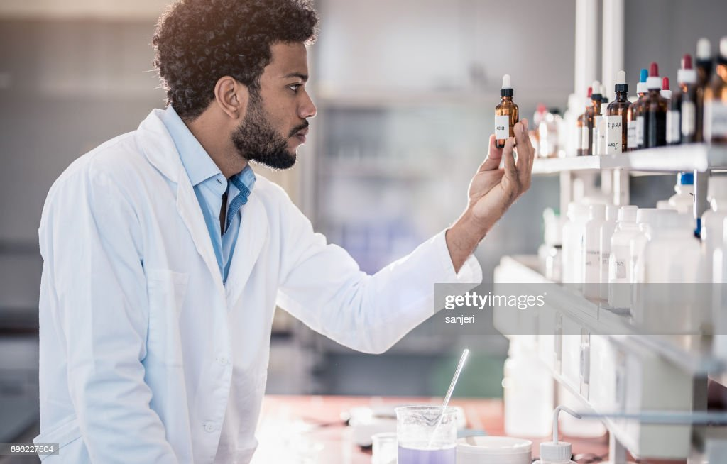Scientist Picking up a Reagent From The Inventory : Stock Photo