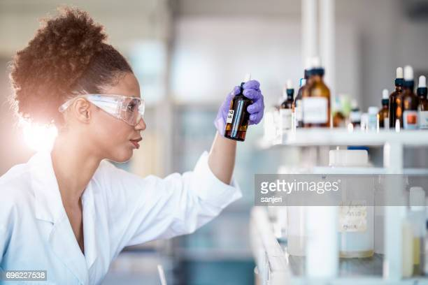 Scientist Picking up a Reagent From The Inventory
