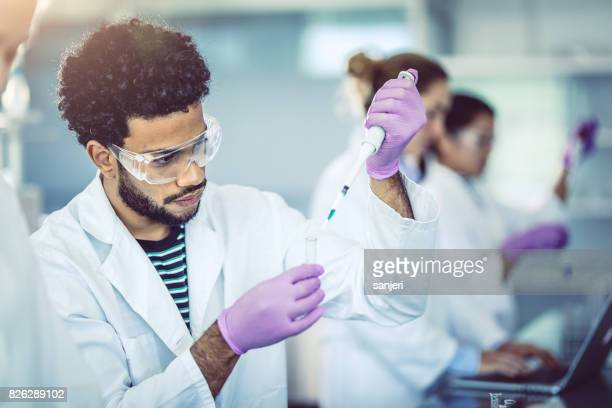 Scientist Pipetting Into Test Tube