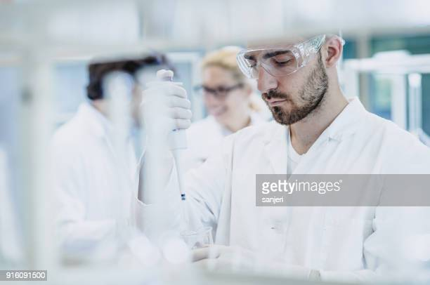 scientist pipetting into test tube - laboratory glassware stock pictures, royalty-free photos & images