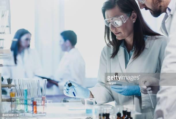 Scientist Placing a Reagent into a Petri Dish